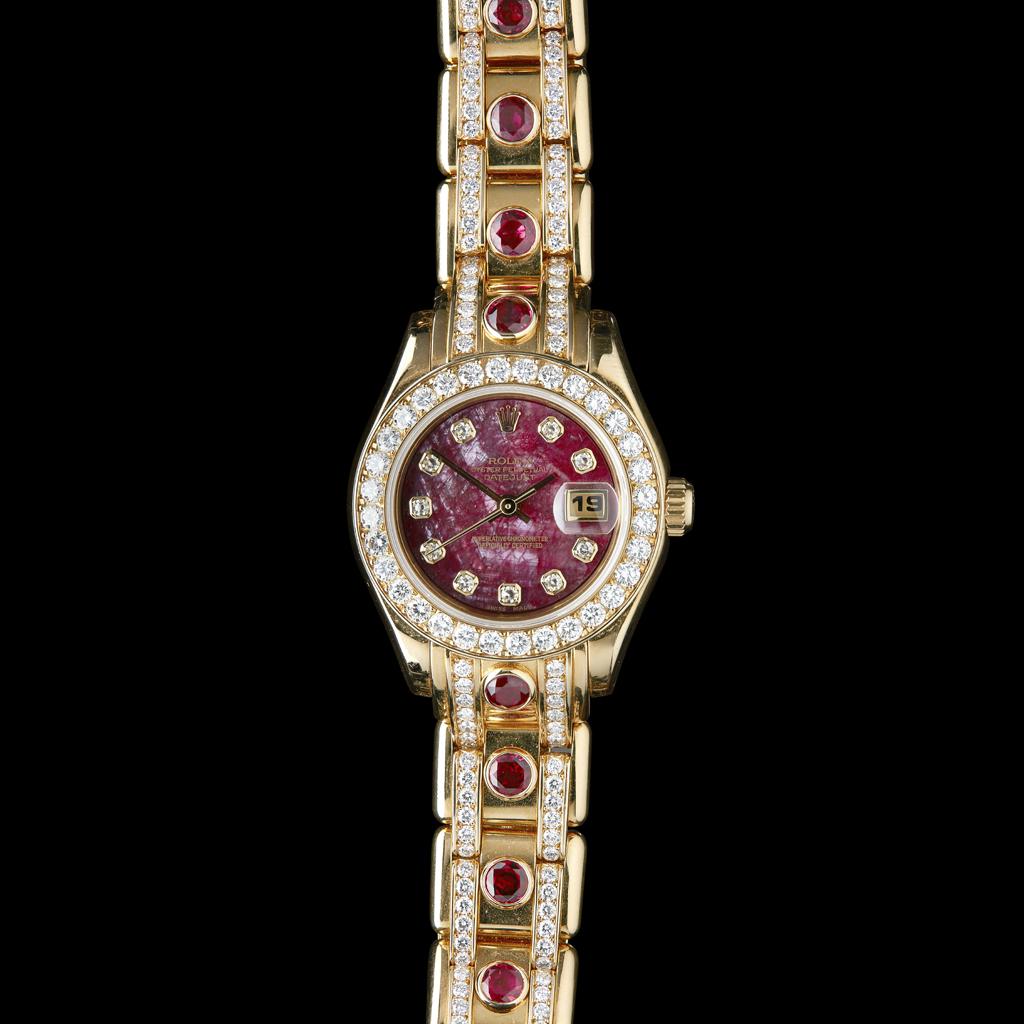 Lot 71 - ROLEX - An 18ct gold ruby and diamond set lady's wrist watch