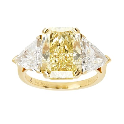 Lot 50 - A fancy yellow and colourless three stone diamond ring, De Beers