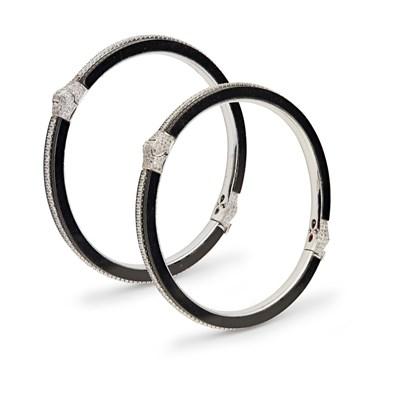 Lot 59 - A pair of onyx and diamond set bangles