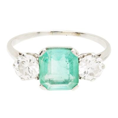 Lot 118 - An emerald and diamond set three stone ring