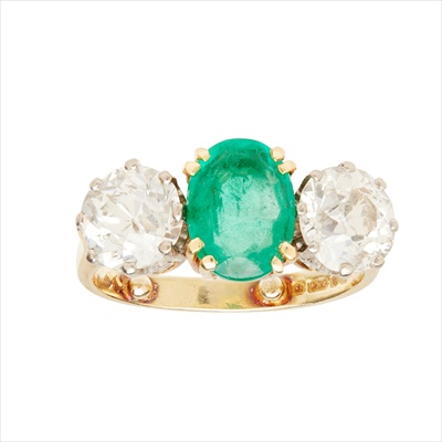 Lot 20-An emerald and diamond set three stone ring